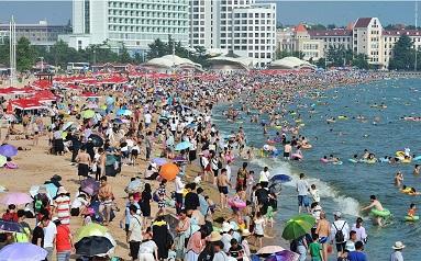 山东高温天气青岛海水浴场近万游客避暑