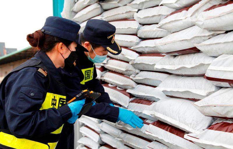 海关关员对固体废物进行取样查验
