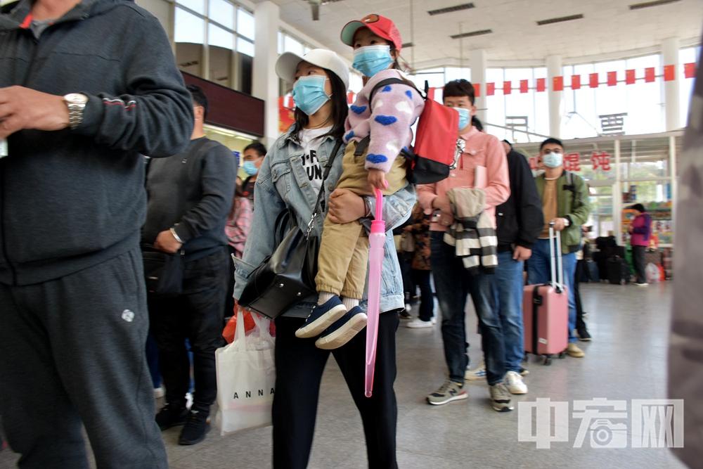 军嫂戴蓉抱着女儿扭扭在蓬长客港排队购票.JPG