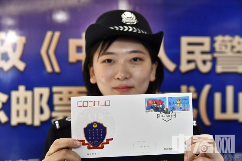 一名民警展示《中国人民警察节》纪念邮票发行首日封0.jpg